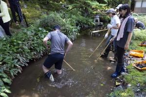 池の底の清掃に汗する学生